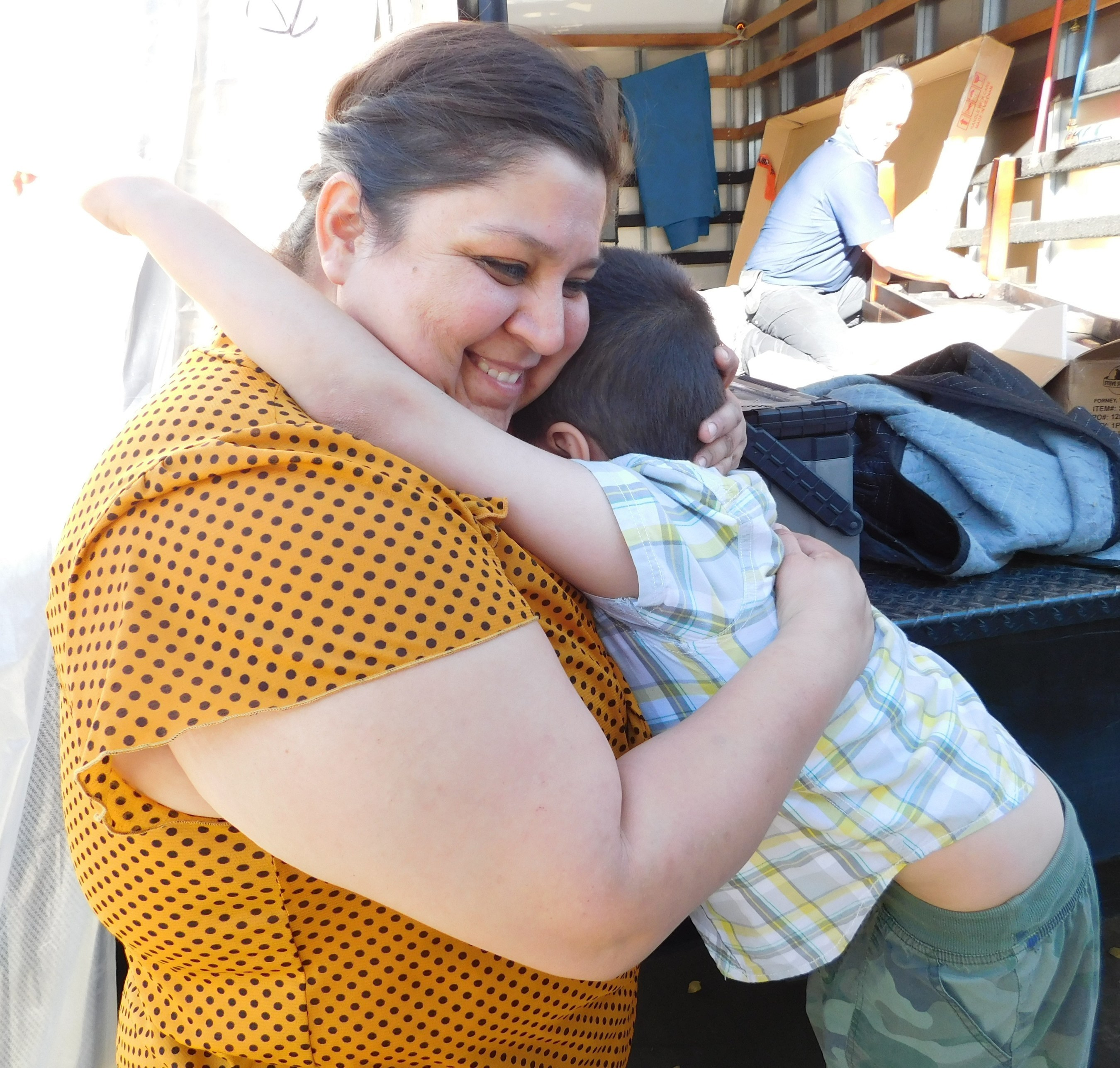 "Maria Sahagun hugs her son with excitement as Aaron's, Inc. associates deliver furniture to fill her entire home on Friday, November 20, 2015, in Rialto, California. Aaron's, Inc., a leader in the sales and lease ownership and specialty retailing of furniture, consumer electronics, home appliances and accessories, in partnership with Univision Network's ""Despierta America,"" surprised Sahagun with new furniture, a prize package valued at more than $24,000, as a part of the first ""Despierta En Tu Nuevo Hogar"" (Wake Up in Your New Home) contest."