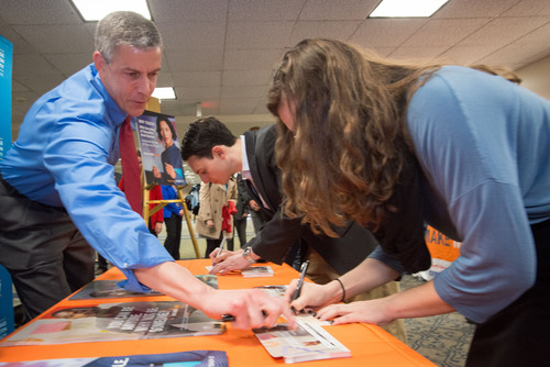 Secretary of Education Arne Duncan (left), assists George Washington University students sign pledge cards promising to learn more about a career in teaching. Today's event is part of TEACH.org's multi-market peer-to-peer recruitment program taking place on 21 college campuses in the U.S. to reach high-achieving young people who might not have otherwise considered a career in education. (PRNewsFoto/TEACH, Ken Cedeno Photography) (PRNewsFoto/TEACH)