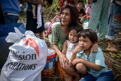 A family receives food, water, and other emergency supplies from World Vision during Thursday's distribution in Tabugon, Philippines.  (PRNewsFoto/World Vision U.S.)