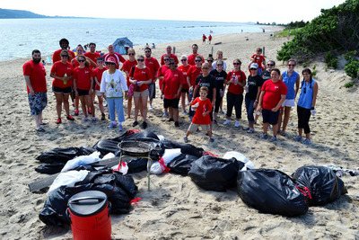 iCIMS volunteers stand proudly behind the bags of litter collected in the Beach Sweep. It was a day of service, education, and fun in the sun.  (PRNewsFoto/iCIMS, Inc.)