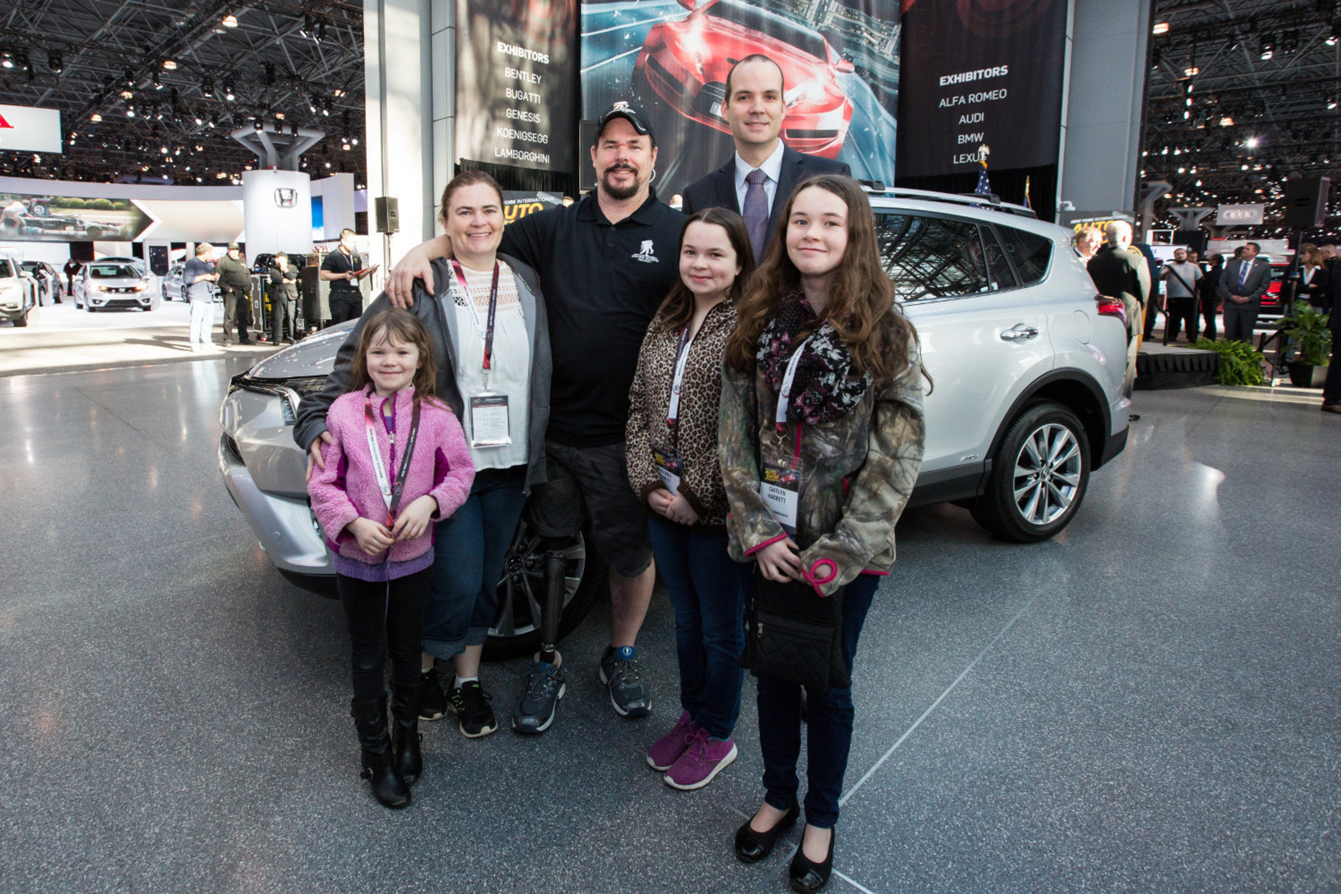 """Army Sergeant First Class Jeffrey Hackett (in hat), who lost his leg during the war in Afghanistan, poses in front of his new RAV4 Hybrid, donated by Toyota during the opening ceremony of the New York International Auto Show. Standing with Hackett and his family is Jason Keller, Toyota vehicle operations manager."""