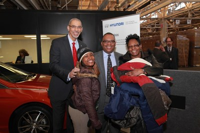 William F. Jones, Jr., Chief Executive Officer of Focus: HOPE (left) and Zafar Brooks, Director of Corporate Social Responsibility at Hyundai Motor America (2nd from right), pose for a photo with a local family during the Hyundai coats for kids event at Focus: HOPE in Detroit, Mich. on Wednesday, Jan. 14, 2015.