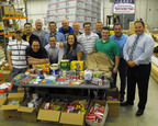 UniFirst Senior Vice President Michael Croatti (right) and 15 company employees enrolled in the UniFirst Management Institute (UMI) packed food and toiletry items for a U.S. Marine Corp. unit in Afghanistan which had been attacked by a suicide bomber, resulting in the loss of their personal supplies. (UniFirst Photo).  (PRNewsFoto/UniFirst Corporation)