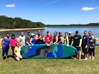 Wounded veterans and their families try stand up paddle boarding.