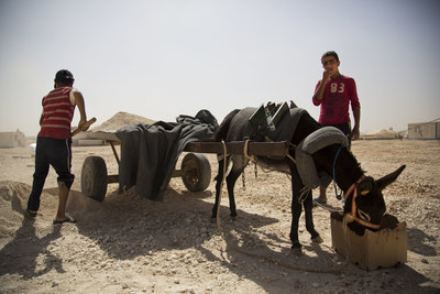 Children work in Za'atari camp digging sand to sell for building material. Photo by Rosie Thompson / Save the Children