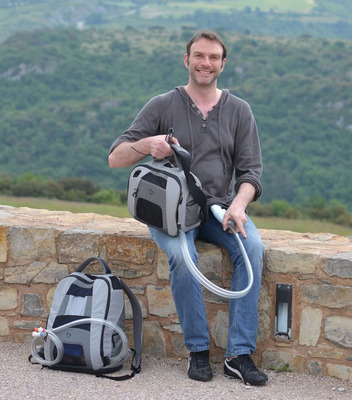 Since his August. 5, 2011 implant, Frederic Thiollet has been supported with the SynCardia Total Artificial Heart for 949 days as of April 1, 2014. In the Shoulder Bag he's holding is the Freedom(R) portable driver, which powers his Total Artificial Heart. The Backpack on the ground contains his back-up Freedom driver and extra batteries.  (PRNewsFoto/SynCardia Systems, Inc.)