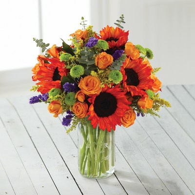"""The Longest Ride"" inspired bouquet delivers the casual elegance of the movie setting with a Mason jar vase filled with bright orange sunflowers and spray roses, highlighted by deep purple statice and sunny solidago."