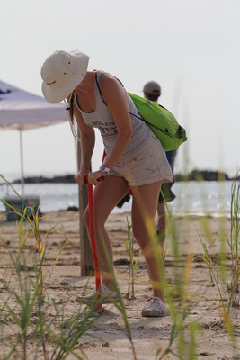 A volunteer at the CITGO-CRCL dune restoration event digs a hole for some of the 65,000 dune grass plugs planted on Constance Beach in Louisiana