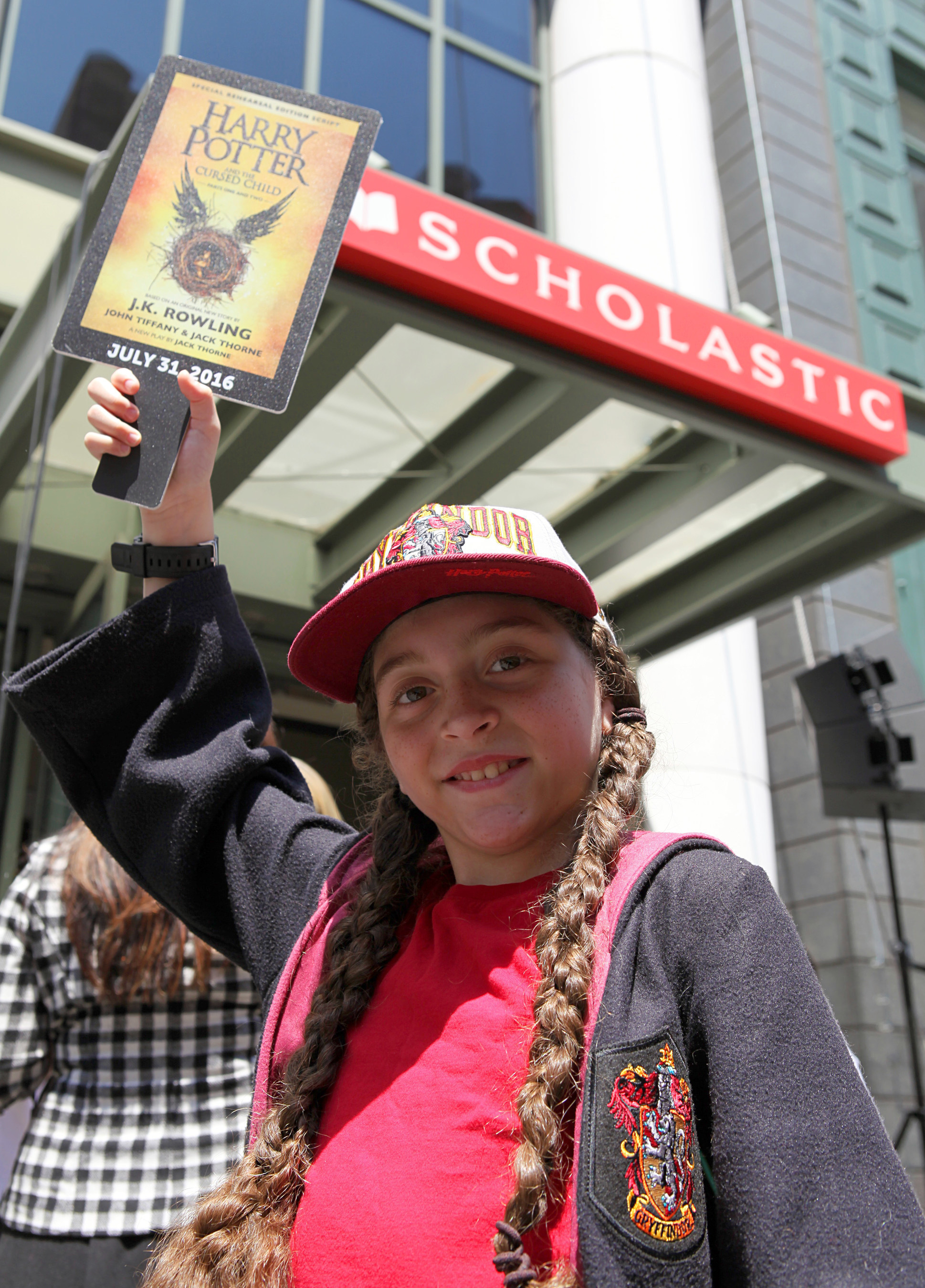 """A Scholastic employee's daughter, 10-year-old Ella, joins the """"Muggle Mob"""" of 300 Harry Potter fans in front of the Scholastic headquarters building in New York City on July 21, celebrating the upcoming release of """"Harry Potter and the Cursed Child Parts One and Two,"""" the eighth story, on July 31, 2016 at 12:01 a.m. ET. Credit: Scholastic"""