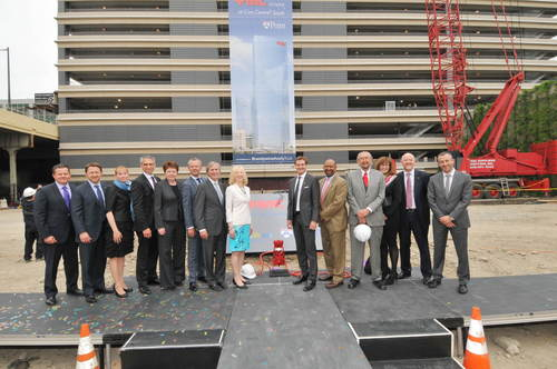 Partners from the private, public and education sectors gather around a vintage vertical pump to mark the ...