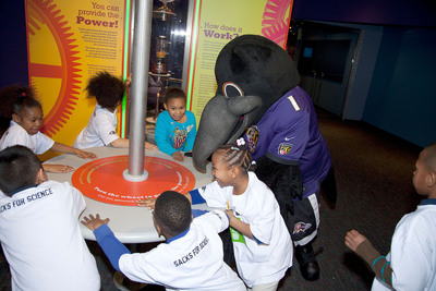 Visiting 1st graders and Poe of the Baltimore Ravens have fun generating power in the newly opened Power Up! exhibit at the Maryland Science Center.