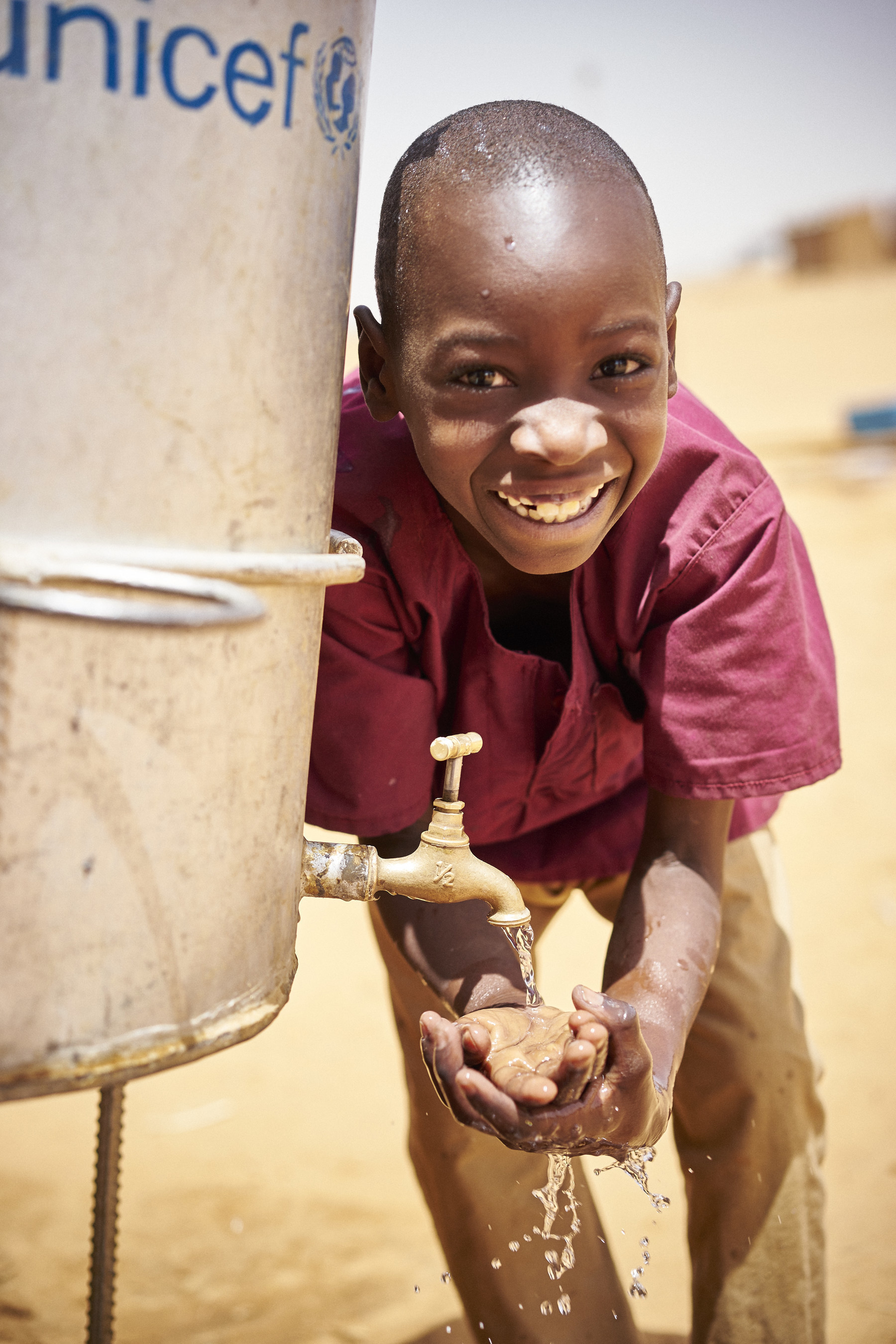 Mohamed Alhoussein, 7 years old, washes his hands outside of his classroom at the Tabareybarey refugee camp,Tillaberi region, Niger. (C) UNICEF/UNI201289/Phelps