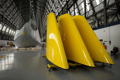 Giant tail fins await in the foreground as the envelope is installed over the framework of the newest Goodyear Blimp, being assembled this summer at Goodyear's Wingfoot Lake Hangar in Suffield, Ohio.  (PRNewsFoto/The Goodyear Tire & Rubber Company)