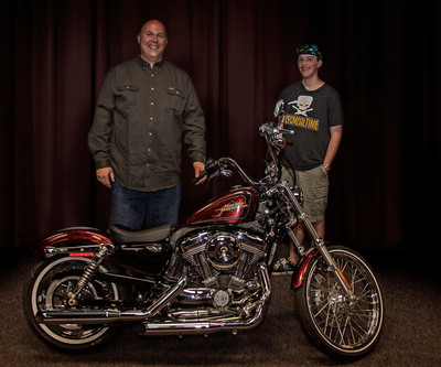 Richard Robison is joined by his son Robbie as they pose with a new Harley-Davidson awarded to Richard by C.R. England.  (PRNewsFoto/C.R. England)