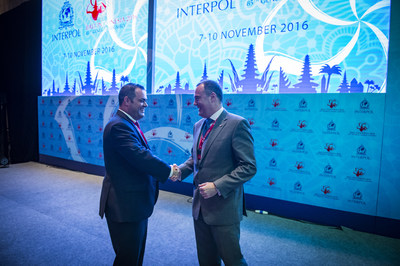 Chris Malo (left), head of global maritime security for Carnival Corporation, and Mick O'Connell (right), director of operational support and analysis for INTERPOL, shake hands following a vote at INTERPOL's General Assembly where Carnival Corporation was announced as the first maritime company to partner with the organization for advanced security screening across its global operations. Carnival Corporation received approval at the Assembly to integrate its global passenger check-in process with...
