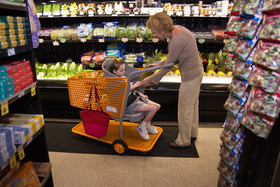 "Drew Ann Long grocery shops with her daughter, Caroline, who sits comfortably in ""Caroline's Cart.""  (PRNewsFoto/Caroline's Cart, John Marc Green)"