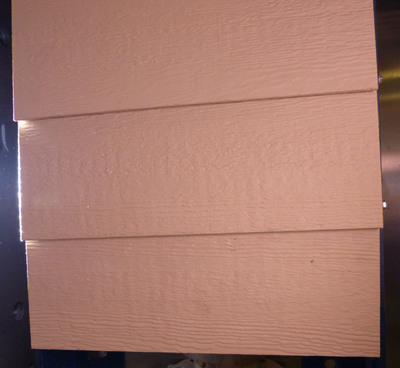 """From the NASA evaluation: """"The impact velocities were 72.8 mph for the fiber cement siding sample and 77.7 mph for the LP® [engineered wood] siding sample. … The fiber cement siding sample sustained a large hole and backside spalling. There was no visual evidence of damage in the LP siding sample [SHOWN HERE]."""""""