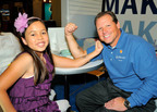 MDA Goodwill Ambassador Abbey Umali makes a muscle with Stu Crum, President of Jiffy Lube International, in anticipation of the Jiffy Lube Muscle Up(SM) campaign.  (PRNewsFoto/Jiffy Lube International, Inc.)