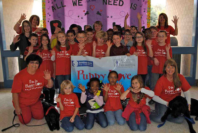 "Mrs. Scott's third grade class at Ocean Lakes Elementary in Virginia Beach, VA welcomes puppies Joanie and Godrick from The Atlantic Shores/Guiding Eyes For The Blind ""Puppy Love Program."" The class is paired with seniors from the Atlantic Shores retirement community, who together are raising and socializing the two puppies for their future as guide dogs. Special curriculum at Ocean Lakes will help third grade students understand the invaluable service these puppies will eventually provide. Student-reporters create segments for their in-classroom TV, and follow the puppies' progress on an Atlantic Shores ""Dog Blog""."
