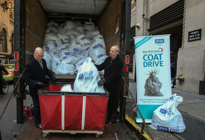 New York Cares executive director (left) and Greater New York Automobile Dealers Association president Mark Schienberg help unload 6,000 coats collected by automobile dealers across the greater New York area.