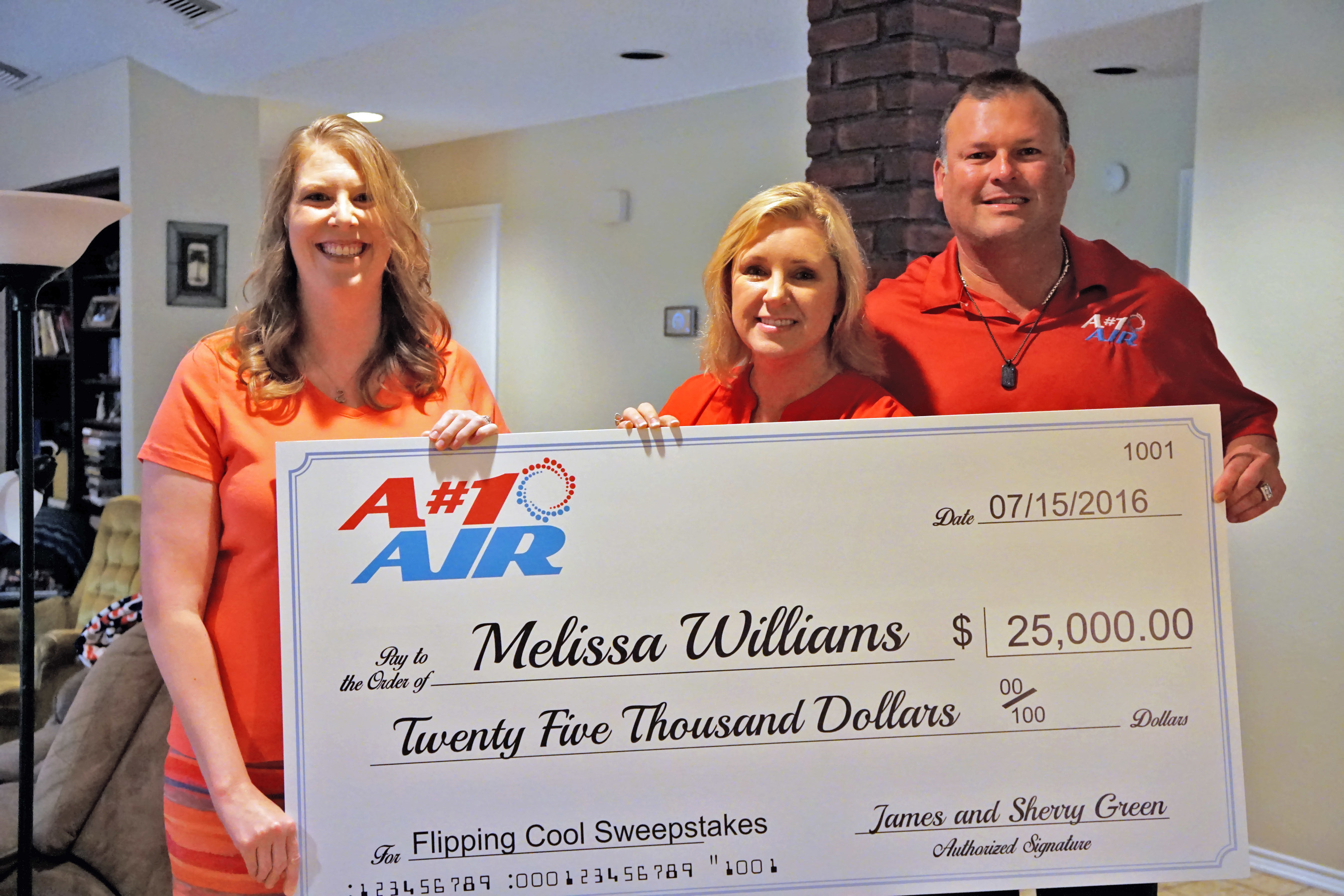 """A#1 Air owners Sherry and James Green present Melissa Williams, winner of the A#1 Air Flippin' Cool Sweepstakes, a $25,000 check. Other prizes she won include a top-of-the-line Lennox 25 SEER Signature Series a/c system, iComfort smart thermostat, tankless water heater, duct cleaning and more. The Flippin' Cool Sweepstakes were sponsored by A#1 Air, Richard Rawlings of the Discovery show """"Fast N' Loud"""" and Lennox. The new a/c system came just in time, as Melissa's was about to go out completely."""