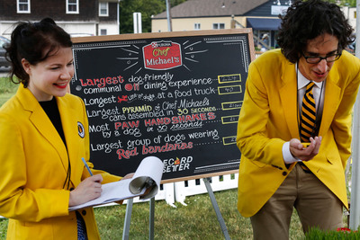RecordSetter officiates another record attempt after declaring Chef Michael's food for dogs as the record holder for the World's Largest Dog-Friendly Communal Dining event, Saturday, June 29, 2013, in Bridgehampton, N.Y. (John Minchillo/AP Images for Chef Michael's).