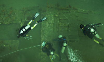 A team of leading U.S. archaeologists study the wreckage of a ship they believe to be part of Captain Henry Morgan's lost fleet. The dive team discovered approximately 52x22 feet of the starboard side of a 17th century wooden ship hull and a series of unopened cargo boxes and chests encrusted in coral. Photo Credit: Captain Morgan / Chris Bickford