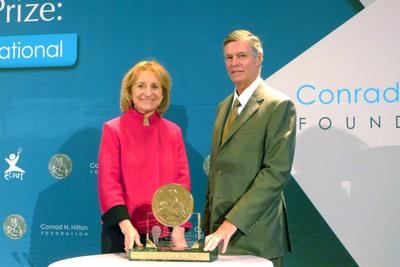Executive Director Dorothy Rozga accepts the 2013 Hilton Humanitarian Prize from Steven M Hilton on behalf of ECPAT International.  (PRNewsFoto/Conrad N. Hilton Foundation)