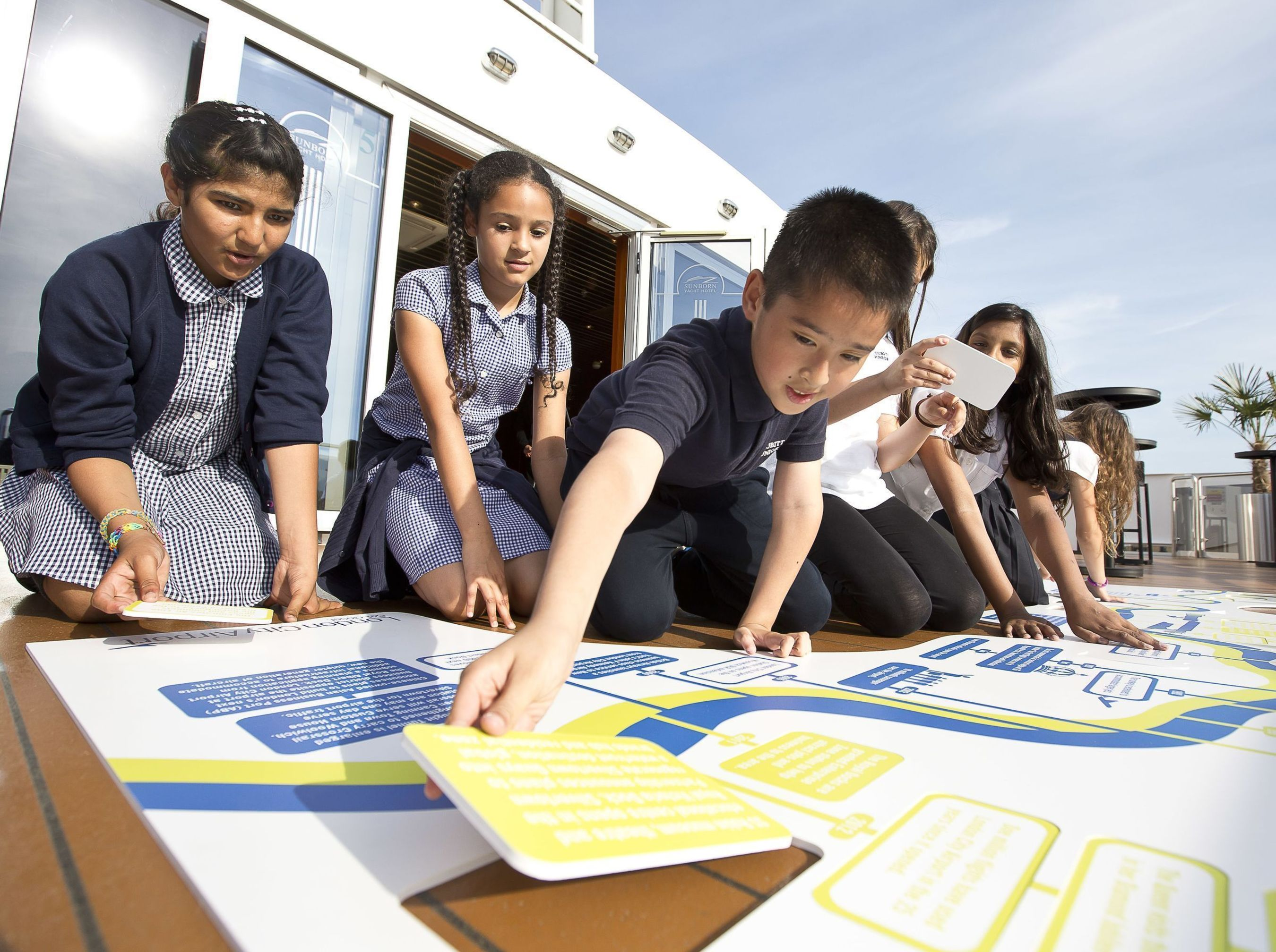 Children from Cubitt Town Junior School learn about the history of London's Royal Docks with a giant timeline puzzle. (PRNewsFoto/London City Airport)
