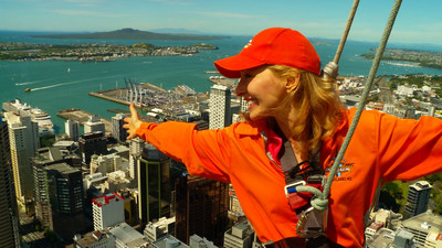 Host Linda Swain walks around the outside of the Skytower, the tallest building in the Southern Hemisphere.