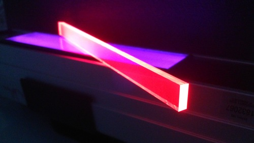 Quantum dot luminescent solar concentrator devices (embedded in the glowing pink bar) under ultraviolet ...