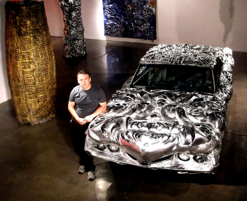 Artist Ioan Florea in front of the 3D printed liquid metal transferred Ford Torino 1971. The entire car is covered in a seamless texture of organic shapes with the highest reflectivity unattainable before. In the left side is the oversized 9 feet tall and 5 feet diameter Cyrus Cylinder contemporary version with Declaration of  Universal Human Rights 3D printed transferred and embedded into it created in similar manner as the ancient artifact. In the background is a 10 feet tall 3D printed liquid metal transferred Nanotube-Nanohaystack based on  ...