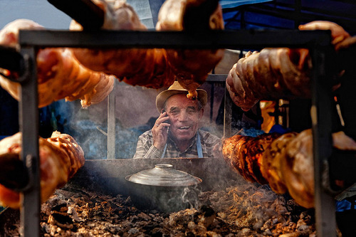 A man sells chicken in the market place while talking on a mobile phone.  (PRNewsFoto/CGAP)