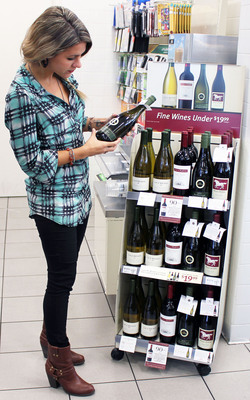 Emily Roff of Dallas checks out the new line-up of wines at a 7-Eleven store in an affluent area where its customers are inclined to buy pricier varietals. (PRNewsFoto/7-Eleven, Inc.) (PRNewsFoto/7-ELEVEN_ INC_)