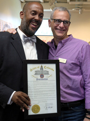 Tyler Mounsey, Director of Constituent Services for Governor Hickenlooper, and Jerry Colonna, Naropa University Board of Trustees Chair, pose with Hickenlooper's proclamation. (PRNewsFoto/Naropa University)