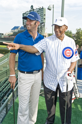 """""""Mr. Cub"""" Ernie Banks shows BMW Championship defending champion Dustin Johnson how to call his shot the way Babe Ruth did after participating in a historic challenge in which the pair attempted to make a hole-in-one in order to earn a $100,000 college scholarship for the Evans Scholars Foundation, a Chicago-based charity.  (PRNewsFoto/BMW Championship, Timothy Hiatt)"""
