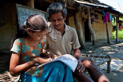 Save the Children Literacy Boost program participant Radhika, 9, practices reading with her grandfather, Makuram Dangaura, 55, outside their home in Rajipur village, Nepal. Save the Children's new report shows that learning, not only in school, but outside the classroom, as well, is key to boosting children's reading skills. Photo by Susan Warner.  (PRNewsFoto/Save the Children)