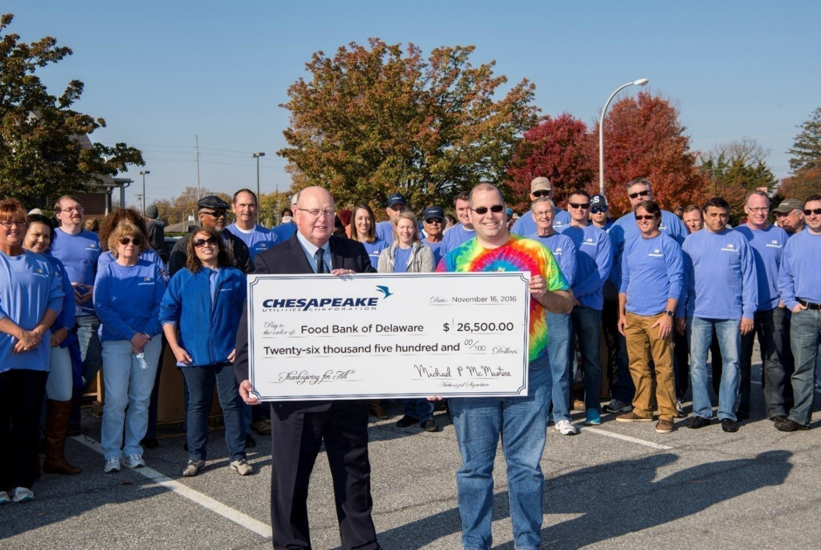 Chad Robinson, Milford Branch Director of the Food Bank of Delaware (right) accepts a donation made on behalf of Chesapeake Utilities Corporation, presented by Michael P. McMasters, Chesapeake Utilities Corporation President and Chief Operating Officer (left).