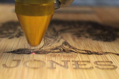 An AP Lazer machine laser engraving an illustration of a tree onto a personalized bamboo cutting board. Photo courtesy of AP Lazer.