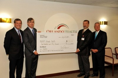 From left to right, David Fuller, president and CEO of SunTrust's Central Florida Division, and Bill Rogers, chairman and CEO of SunTrust Banks, Inc., present a $250,000 gift to Orlando Health's interim president and CEO, Jamal Hakim, MD, and senior vice president, John Bozard, to help support Orlando Regional Medical Center's redesign and renovation project.