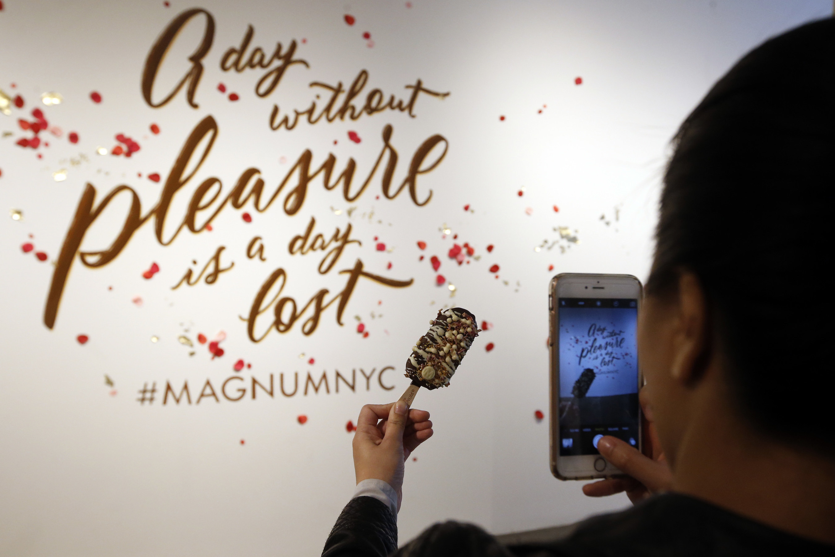 """A guest at MAGNUM New York captures a close-up photo of a custom MAGNUM Ice Cream bar. At the store's """"dipping bar,"""" guests can create custom MAGNUM bars with a selection of decadent ingredients, including rose petals, espresso sugar and gogi berries. This is the first U.S. storefront for MAGNUM Ice Cream and it's located at 134 Prince Street in SoHo; for more information, visit Facebook.com/MAGNUM. (Photo by Jason DeCrow for MAGNUM)"""