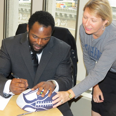 Seattle Seahawk Running Back Robert Turbin finalizes his philanthropic partnership with Seattle Foundation and the formation of his Runnin4U Foundation, which will benefit individuals with multiple sclerosis or cerebral palsy.  Pictured is Turbin and Fidelma McGinn, Vice President/Philanthropic Services at Seattle Foundation.