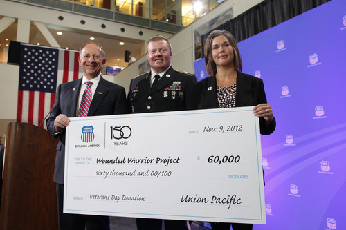 Union Pacific CEO Jack Koraleski (left) presents a $60,000 check to Teresa Nichols from Wounded Warrior Project during a Veterans Day celebration at UP headquarters in Omaha, Neb. As part of its 150th anniversary year celebration, Union Pacific donated tax credit proceeds from a one-time federal incentive program for vets meeting certain criteria. One of the veterans UP hired as part of the federal program is 10-year Army veteran Nate Searls (center), who now works for Union Pacific in North Platte, Neb.  (PRNewsFoto/Union Pacific)