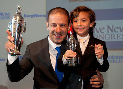 2013 Indianapolis 500 winner Tony Kanaan received his first BorgWarner Championship Driver's Trophy(TM) during the 2014 Automotive News World Congress. As a special surprise, his son, Leo, received a mini Baby Borg.  (PRNewsFoto/BorgWarner Inc./Pat Bafile, P.B. Photographics)