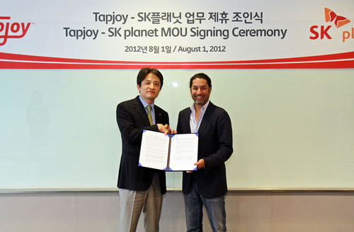 Tapjoy CEO Mihir Shah (right) and SK Planet's T Store vice president Jung Min Park(left) sign a memorandum ...