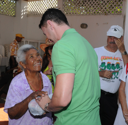A Crystal volunteer offers supplies to a villager in Cartagena, Columbia. (PRNewsFoto/Crystal Cruises) ...