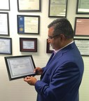 Parkway Clinical Laboratories CEO, Dr Raza Bokhari, proudly inspects NY State lab permit.