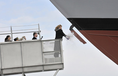 Mrs. Mary Winnefeld, ship sponsor of the future USS Sioux City, christens the 11th littoral combat ship before launching sideways into the Menominee River in Marinette, Wis.