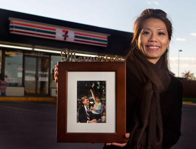 7-Eleven franchisee Phuong Duong outside her store in Austin, Texas, shows off her photo taken with Vice President Dan Quayle in 1989. Phuong and her family escaped war-torn Vietnam and spent four years in a Malaysian refugee camp.  The picture of her waving the American flag was used by news media around the world and was the start of Phuong's path to the U.S. and business ownership.  (PRNewsFoto/7-Eleven, Inc.)