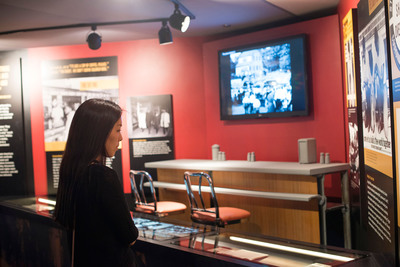 """A Newseum visitor reads about the F.W. Woolworth lunch counter where in 1960 four African-American college students launched the sit-in movement. """"Make Some Noise: Students and the Civil Rights Movement"""" opens Aug. 2.  (PRNewsFoto/Newseum)"""